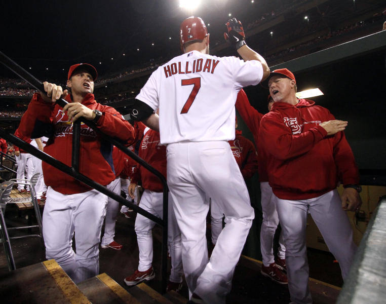St. Louis Cardinals' Matt Holliday is congratulated by manager Mike Matheny, left, and hitting coach Mark McGwire, right, after driving in a run with a sacrifice fly during the first inning of a baseball game against the Cincinnati Reds on Tuesday, Oct. 2, 2012, in St. Louis. (AP Photo/St. Louis Post-Dispatch, Chris Lee) EDWARDSVILLE INTELLIGENCER OUT; THE ALTON TELEGRAPH OUT.