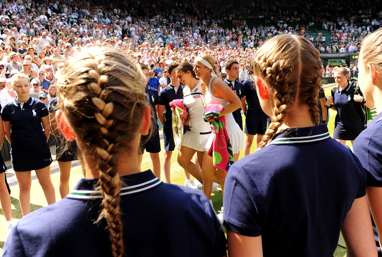France's Marion Bartoli and runner up Germany's Sabine Lisicki (right) walk off after collecting their trophies from the Ladies' Singles Final during day twelve of the Wimbledon Championships at The All England Lawn Tennis and Croquet Club, Wimbledon.