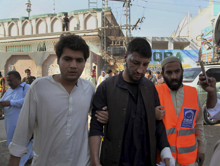 Pakistani volunteers help an injured person at the site of a bomb explosion in an Islamic seminary, in Peshawar, Pakistan, Tuesday, Oct. 27, 2020. A powerful bomb blast ripped through the Islamic seminary on the outskirts of the northwest Pakistani city of Peshawar on Tuesday morning, killing some students and wounding dozens others, police and a hospital spokesman said. (AP Photo/Muhammad Sajjad)