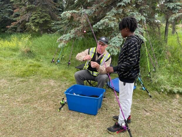 A supervisor gets bait on a line for a child learning to fish for the first time in Edmonton on Saturday. (Emily Fitzpatrick/CBC - image credit)