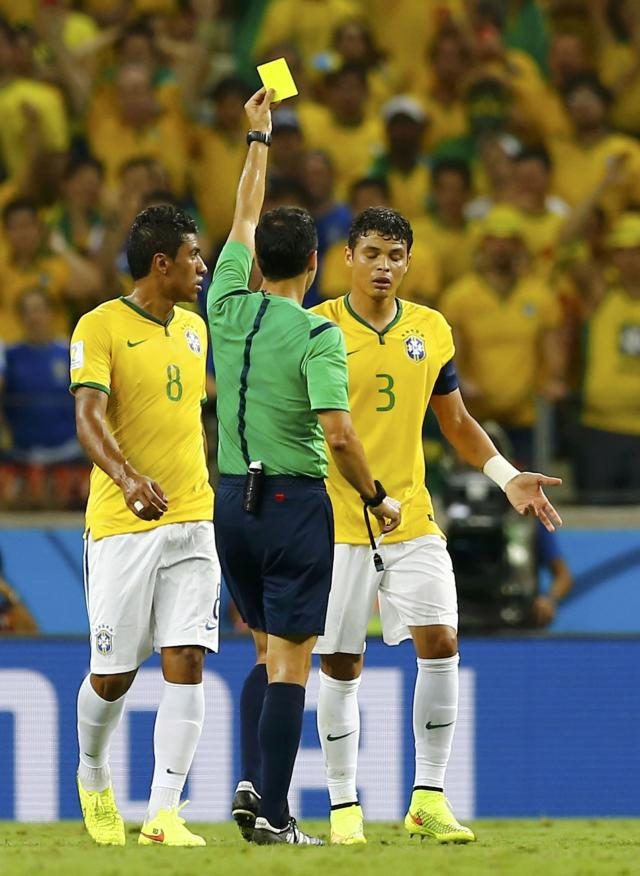 Referee Carlos Velasco Carballo of Spain shows Brazil's Thiago Silva the yellow card during the 2014 World Cup quarter-finals between Brazil and Colombia at the Castelao arena in Fortaleza July 4, 2014. REUTERS/Marcelo Del Pozo (BRAZIL - Tags: TPX IMAGES OF THE DAY SOCCER SPORT WORLD CUP)