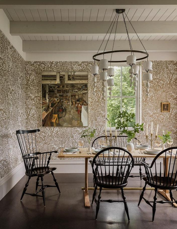 """The dining room is adorned with a Marthe Armitage wallpaper. The chandelier was designed by Helgerson, and the table was designed and made by Doulis. The dining seats are from Great Windsor Chairs. Speaking of the house at large, Helgerson reflects, """"It has a formality at first glance that we think reveals itself to be both livable and gracious."""""""