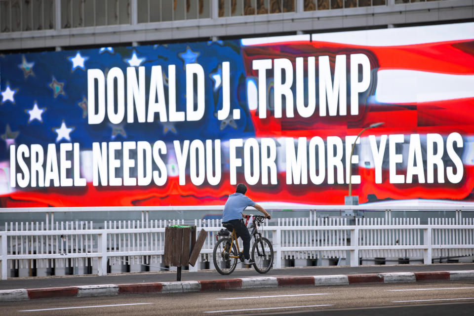 A cyclist rides next to a billboard supporting President Donald Trump, ahed of the U.S presidential election, in Tel Aviv, Israel, Wednesday, Oct. 21, 2020. (AP Photo/Oded Balilty)