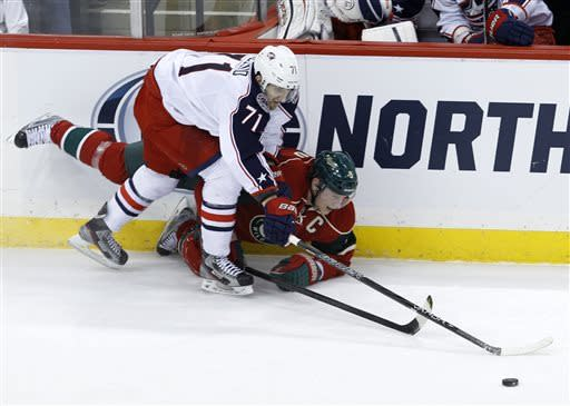 Columbus Blue Jackets left wing Nick Foligno (71) and Minnesota Wild center Mikko Koivu (9), of Finland, battle for the puck during the first period of an NHL hockey game in St. Paul, Minn., Saturday, April 13, 2013. (AP Photo/Ann Heisenfelt)