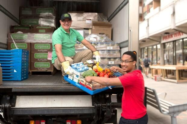 People hand off a pallet of food in this promotional photo by Second Harvest. The group collects excess food that would otherwise go to waste and delivers it to non-profit organizations. (Second Harvest - image credit)
