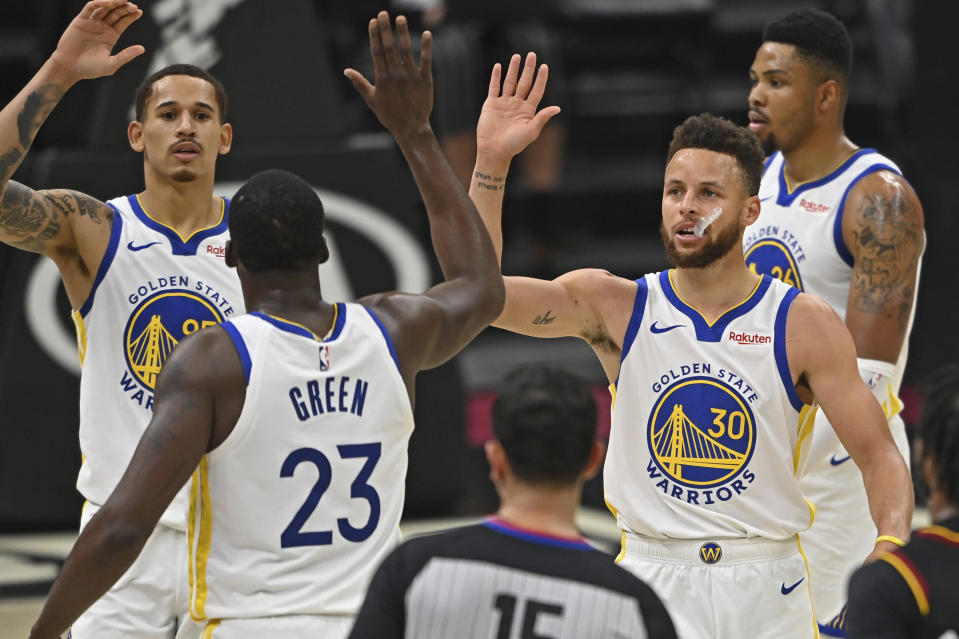 Golden State Warriors' Stephen Curry (30) and Draymond Green (23) celebrate before being substituted out of an NBA basketball game in the second half against the Cleveland Cavaliers, Thursday, April 15, 2021, in Cleveland. (AP Photo/David Dermer)