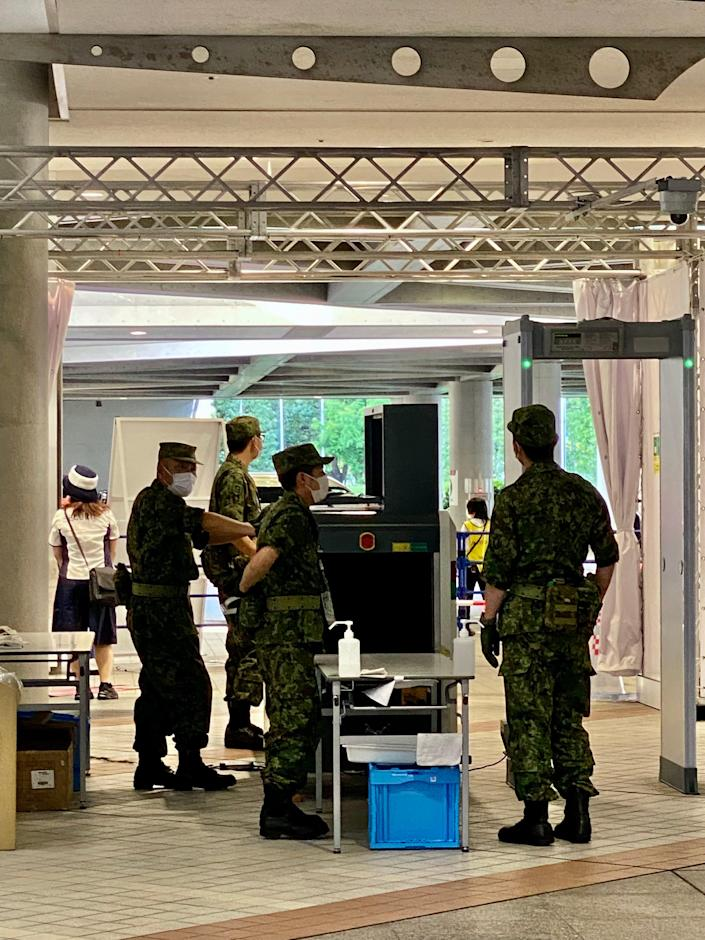 Japan's Self-Defense Forces (JSDF) operate a metal detector and baggage scanner outside the Main Press Center at the Tokyo Olympics.
