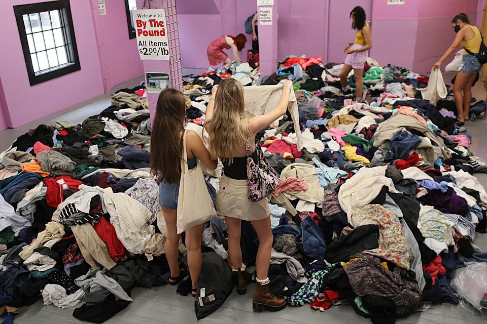 Cambridge, MA - August 18: The pay by pound section of the Garment District thrift shop in Cambridge, MA has opened for the first time during the pandemic. Thrifters sift through the pile of clothing on August 18, 2021. (Photo by Suzanne Kreiter/The Boston Globe via Getty Images)