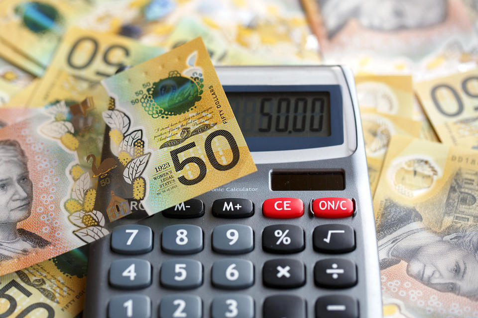 Australian fifty dollar bill over a calculator. The new issue is designed to deter counterfeiting, the note is polymer and water resistant with a clear holographic strip.