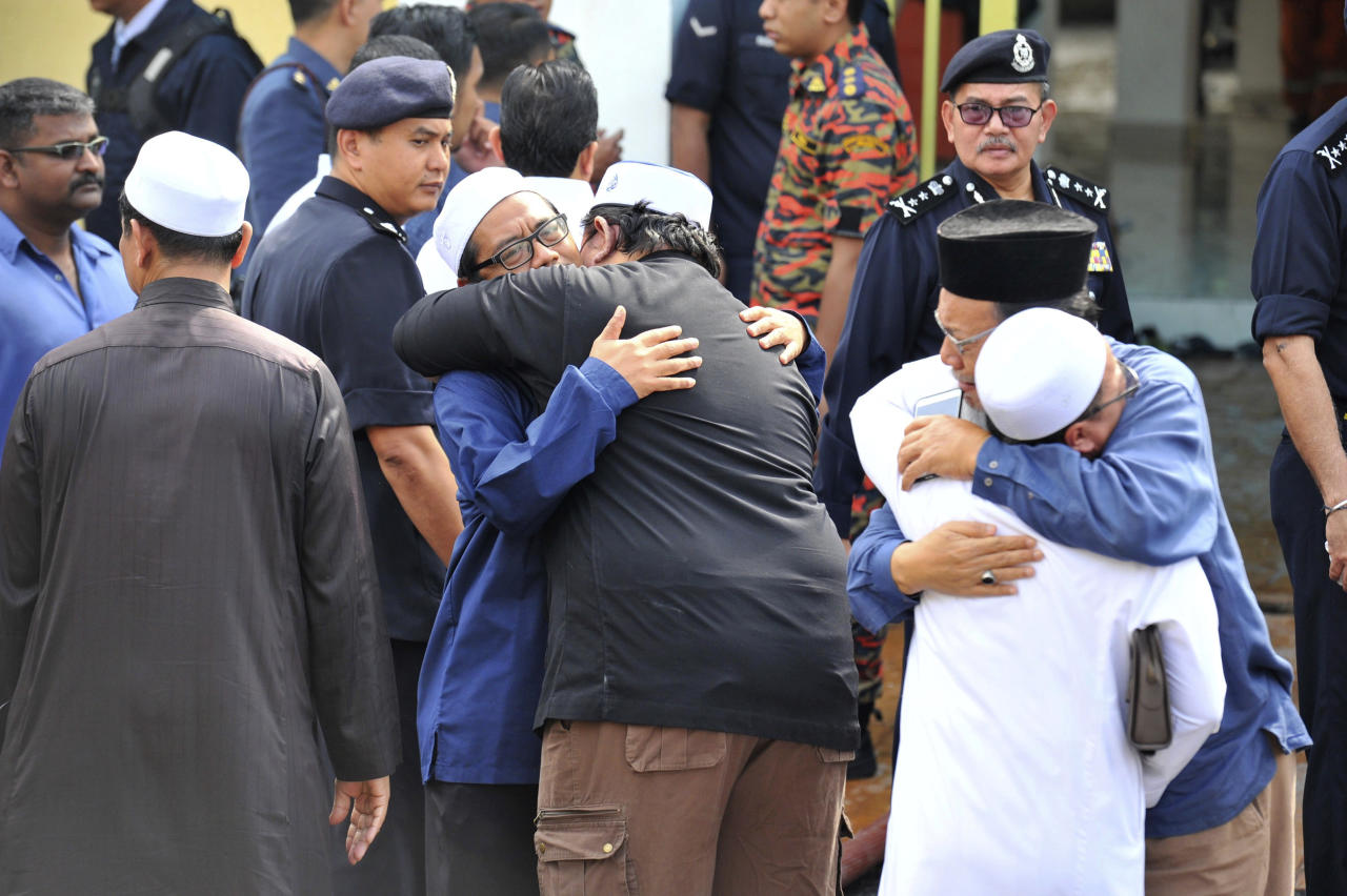 <p>Unidentified Muslim hug each other outside an Islamic religious school following a fire on the outskirts of Kuala Lumpur Thursday, Sept. 14, 2017. (Photo: AP) </p>