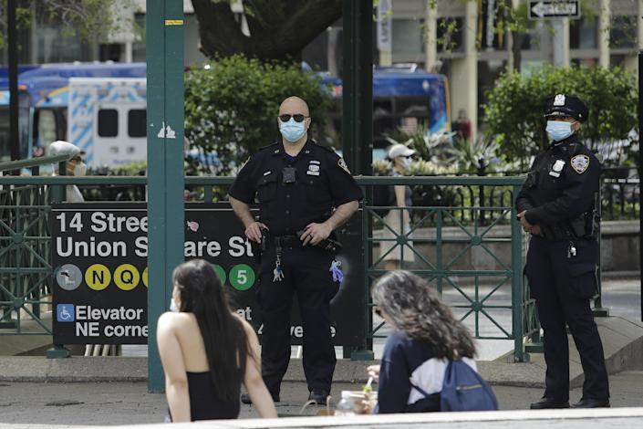Police officers stand watch near the Union Square subway station during the coronavirus pandemic May 2 in New York.
