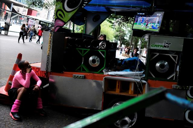 A woman watches Champions League Round of 16 First Leg between Chelsea and FC Barcelona on the TV of Lucena (not pictured) who recycles used materials on his cart in Sao Paulo, Brazil, February 20, 2018. REUTERS/Nacho Doce