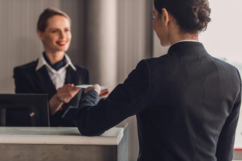 A businesswoman checks in at a hotel lobby reception.