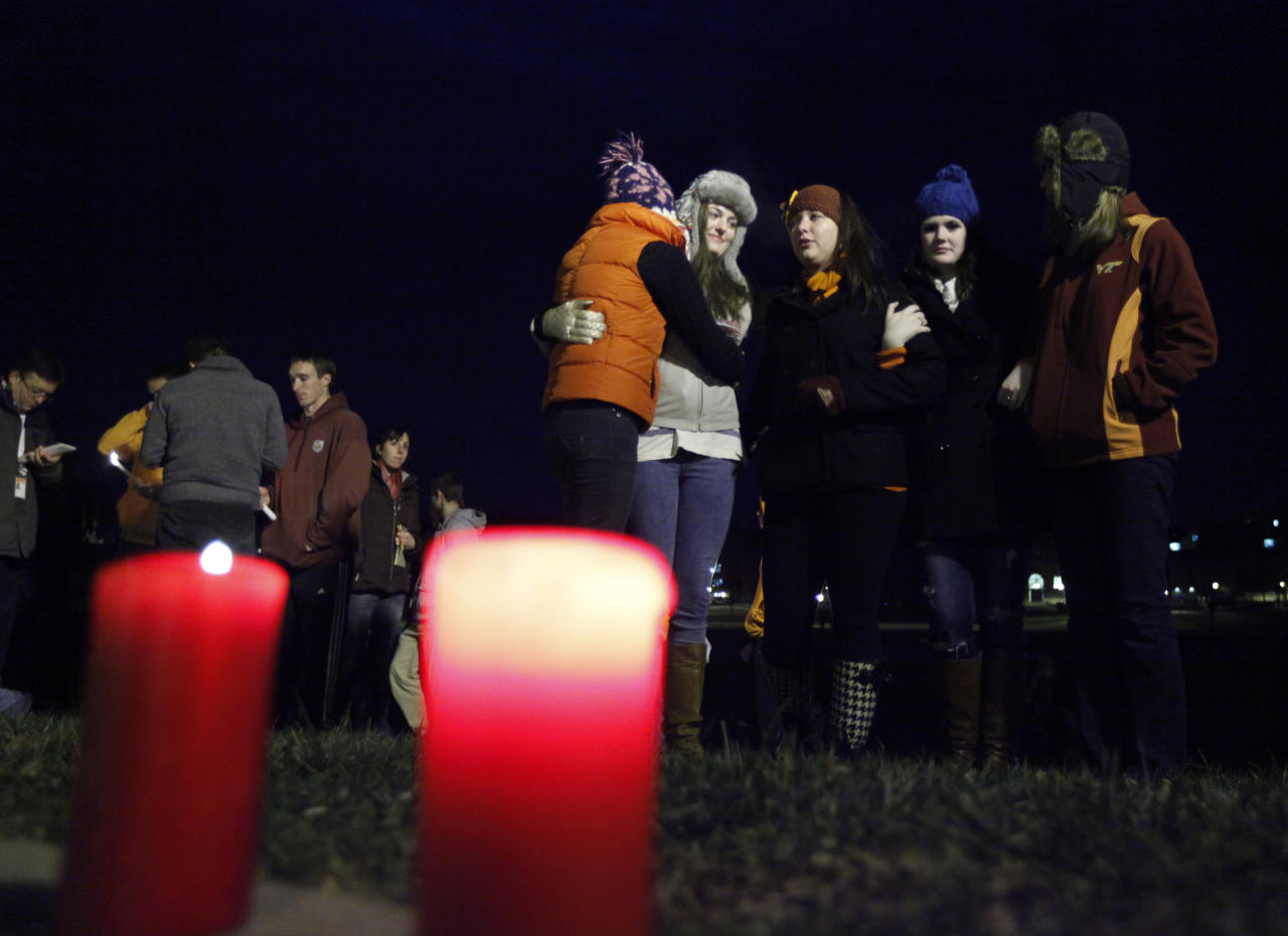Students participate in an impromptu candlelight vigil in front of the 4/16 memorial on the campus of Virginia Tech after two shootings on the campus in Blacksburg, Va., Thursday, Dec. 8, 2011. A gunman killed a police officer and then apparently shot himself to death nearby in a baffling attack that shook up the campus nearly five years after it was the scene of the deadliest shooting rampage in modern U.S. history. (AP Photo/Steve Helber)