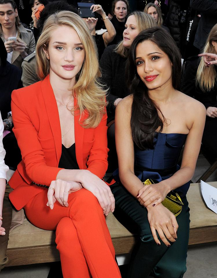 <p>LONDON, ENGLAND - FEBRUARY 18: Rosie Huntington-Whiteley (L) and Freida Pinto sit in the front row for the Burberry Prorsum Autumn Winter 2013 Womenswear Show at Kensington Gardens on February 18, 2013 in London, England. (Photo by Dave M. Benett/Getty Images)</p>