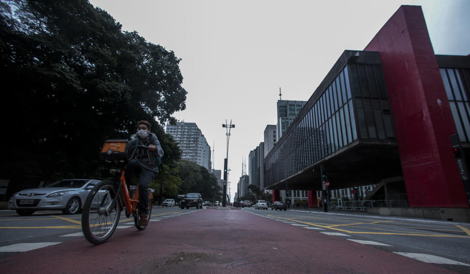 SAO PAULO, BRAZIL - MAY 07: A boy wearing a face mask rides a bicycle at the Paulista Avenue amidst the Coronavirus (COVID - 19) pandemic on May 7, 2020 in Sao Paulo, Brazil. The Government of the State of São Paulo has decreed the mandatory use of face masks in the streets. (Photo by Miguel Schincariol/Getty Images)