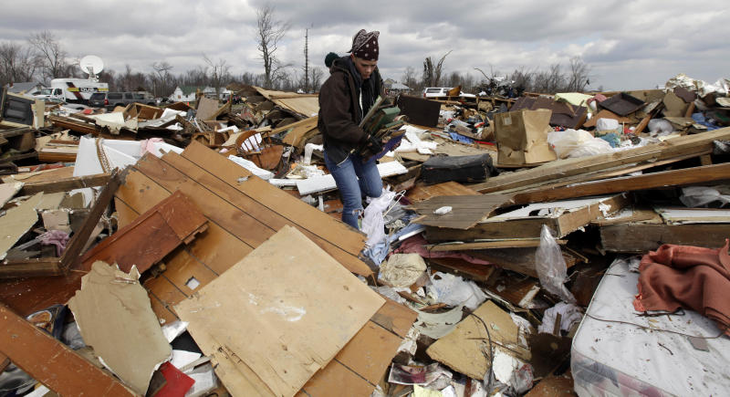 Christa Suchowski search through a home destroyed by a tornado in Marysville, Ind., Sunday, March 4, 2012. Calm weather gave dazed residents of storm-wracked towns a respite on Sunday as they dug out from a chain of tornadoes that cut a swath of destruction from the Midwest to the Gulf of Mexico, killing at least 39 people. (AP Photo/Nam Y. Huh)