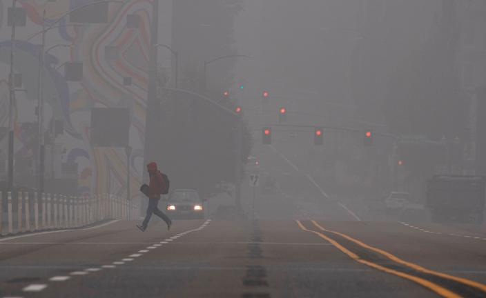 A man crosses a street in downtown Portland, Oregon as wildfires continue to burn in many parts of the state, September 14, 2020. Smoke from wildfires and fog are blanketing the city.