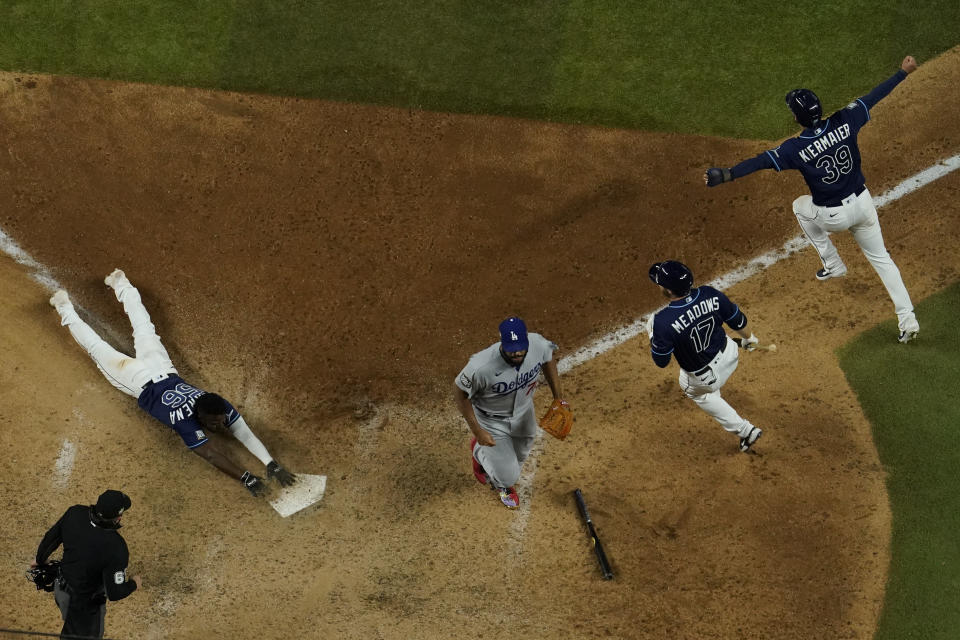 Tampa Bay Rays' Randy Arozarena touches after scoring the winning run against the Los Angeles Dodgers in Game 4 of the baseball World Series Saturday, Oct. 24, 2020, in Arlington, Texas. Rays defeated the Dodgers 8-7 to tie the series 2-2 games. (AP Photo/David J. Phillip)