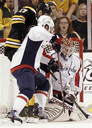 Washington Capitals goalie Braden Holtby makes a save as teammate Karl Alzner tries to clear out Boston Bruins' Milan Lucic during the first period of Washington's 4-3 win in Game 5 in a first-round NHL Stanley Cup playoff hockey series in Boston Saturday, April 21, 2012. (AP Photo/Winslow Townson)