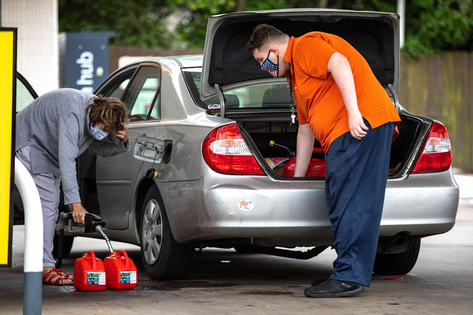Motorists fill up gas cans at a Shell station in Charlotte, North Carolina on May 12, 2021. Fears the shutdown of the Colonial Pipeline because of a cyberattack would cause a gasoline shortage led to some panic buying and prompted US regulators on May 11, 2021, to temporarily suspend clean fuel requirements. (Photo by Logan Cyrus / AFP)