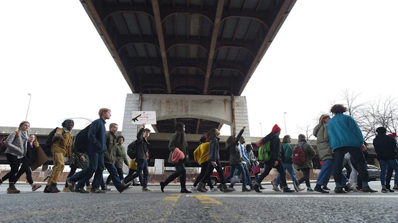 Students from Baltimore School for the Arts walk along Guilford Avenue on their way to City Hall on Tuesday.