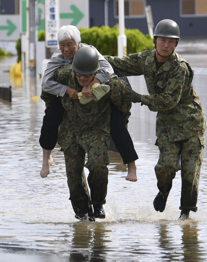 An evacuee is helped by Japan Self-Defense Forces' members as the city is hit by Typhoon Hagibis, in Motomiya, Fukushima prefecture, northern Japan, Sunday, Oct. 13, 2019. Rescue efforts for people stranded in flooded areas are in full force after a powerful typhoon dashed heavy rainfall and winds through a widespread area of Japan, including Tokyo.(Kyodo News via AP)