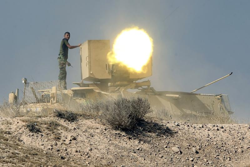An Iraqi Shiite fighter from the Popular Mobilisation units, fighting alongside Iraqi forces, fires a heavy machine gun during a military operation against IS group jihadists as they advance towards the centre of Baiji, Iraq on October 18, 2015 (AFP Photo/Ahmad Al-Rubaye)
