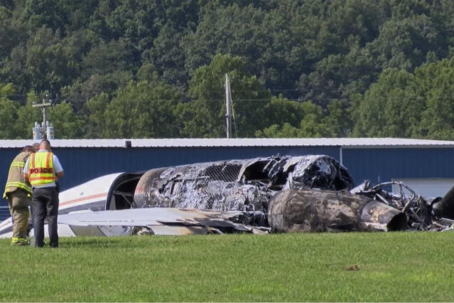 """The burned remains of a plane that was carrying NASCAR television analyst and former driver Dale Earnhardt Jr. lies near a runway Thursday, Aug. 15, 2019, in Elizabethton, Tenn. Officials said the Cessna Citation rolled off the end of a runway and caught fire after landing at Elizabethton Municipal Airport. Earnhardt's sister, Kelley Earnhardt Miller, tweeted that """"everyone is safe and has been taken to the hospital for further evaluation."""" (WJHL TV via AP)"""