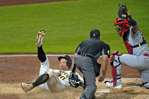 Pittsburgh Pirates' Bryan Reynolds, left, is tagged out by St. Louis Cardinals catcher Yadier Molina, right, with umpire Robert Ortiz preparing to make the call during the sixth inning of a baseball game in Pittsburgh, Thursday, Sept. 17, 2020. (AP Photo/Gene J. Puskar)