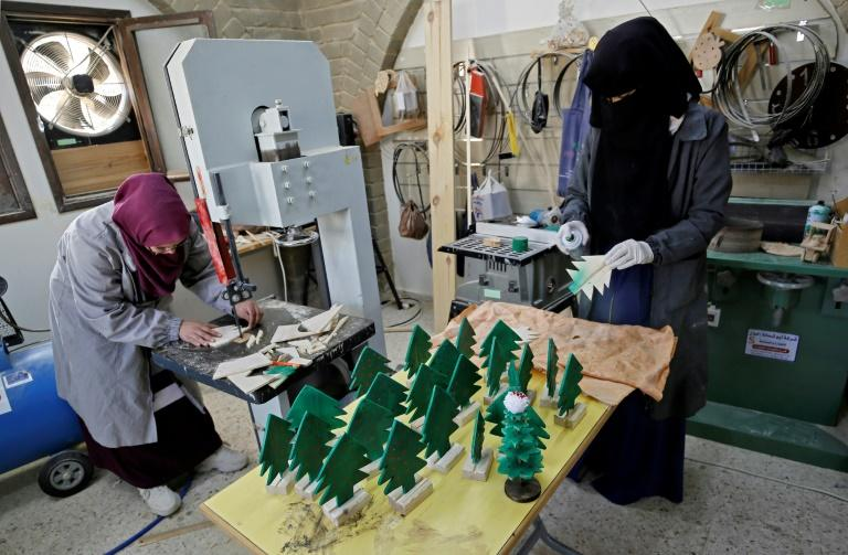 Seven of the women in the project have been taught carpentry and make wooden Christmas trees for the gift boxes sold during over the holiday (AFP Photo/MOHAMMED ABED)