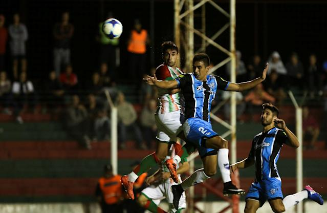 Agropecuario's Cristian Barinaga (C) and Almagro's Ariel Coronel jump for a header during their Argentine Second Division match at Ofelia Rosenzuaig stadium in Carlos Casares, Argentina, April 16, 2018. Picture taken April 16, 2018. REUTERS/Agustin Marcarian