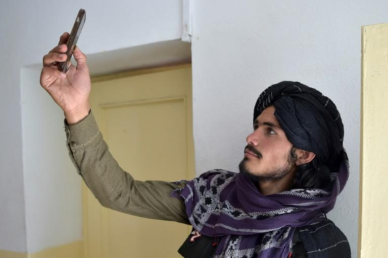 A Taliban fighter searches for a network signal in Ghazni province