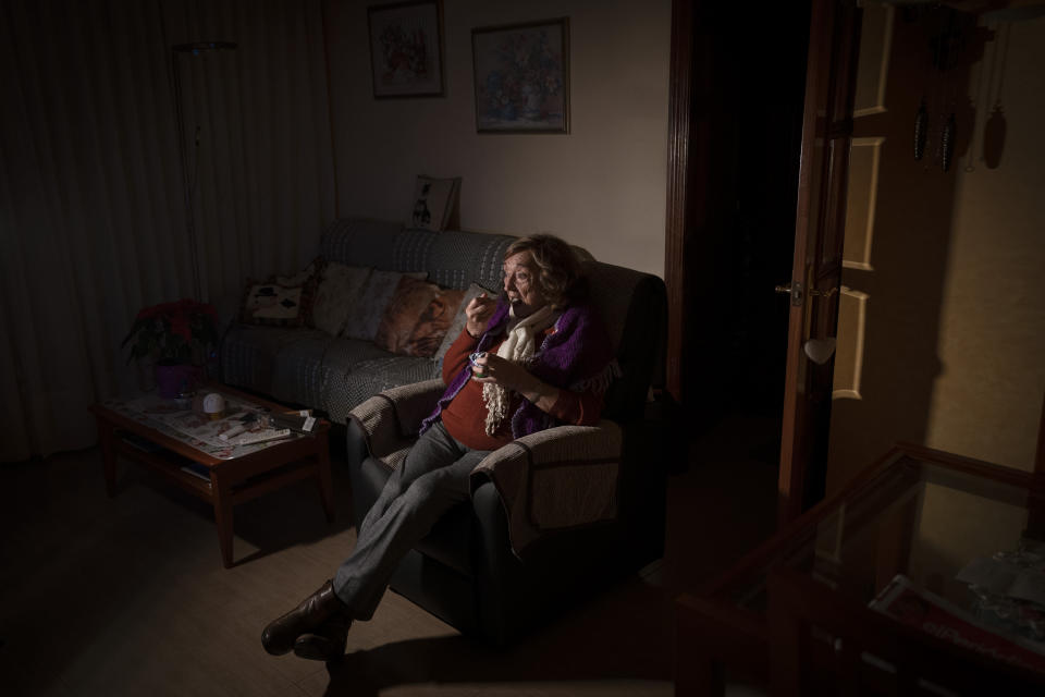 Montserrat Parello watches television while eating a yogurt for Christmas Eve dinner at her home in Barcelona, Spain, Thursday, Dec. 24, 2020. Many of Barcelona's elderly poor who live alone feel more isolated than ever on a Christmas Eve without family or friends due to pandemic restrictions in Spain. For these seniors, the night before Christmas will consist of a yogurt or a cold sandwich without more company than, perhaps, the television. (AP Photo/Emilio Morenatti)