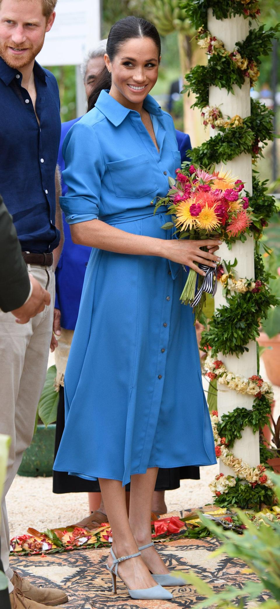 """<p>Meghan first wore <a href=""""https://www.popsugar.com/fashion/Meghan-Markle-Blue-Veronica-Beard-Dress-Tonga-2018-45423452"""" class=""""link rapid-noclick-resp"""" rel=""""nofollow noopener"""" target=""""_blank"""" data-ylk=""""slk:this cornflower-blue Veronica Beard shirtdress"""">this cornflower-blue Veronica Beard shirtdress</a> for the unveiling of The Queen's Commonwealth Canopy at Tupou College in in Nuku'alofa, Tonga, during her and Prince Harry's royal tour of Australia, Fiji, Tonga, and New Zealand in October 2018. </p>"""
