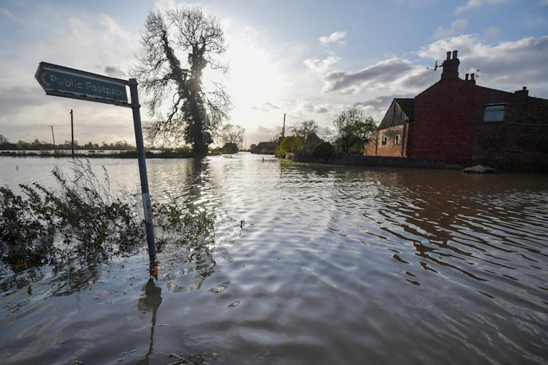A public footpath sign is seen beside a flooded farm on the road to Fishlake (Getty Images)