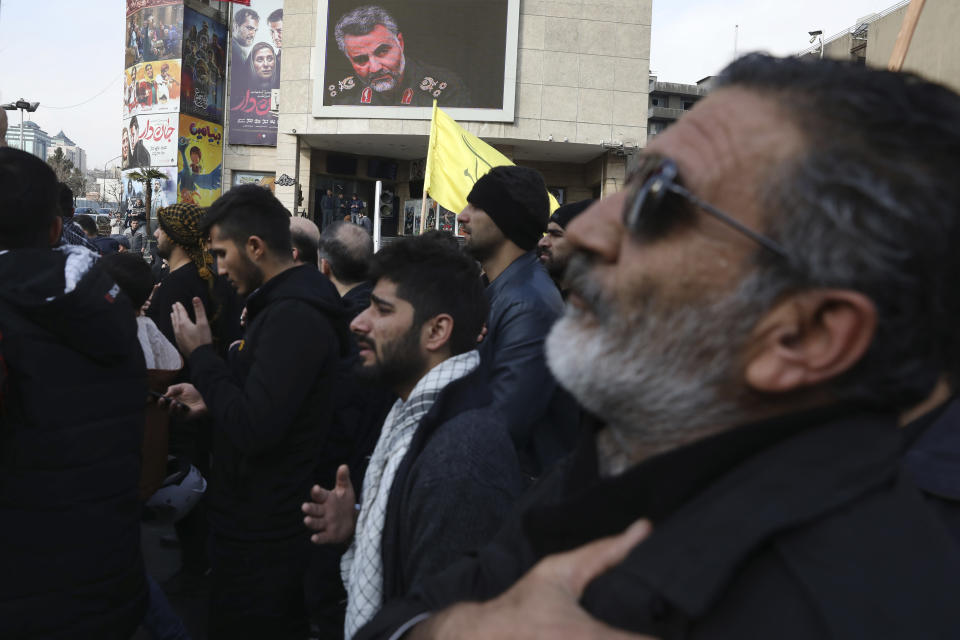 """Protesters mourn in a demonstration over the U.S. airstrike in Iraq that killed Iranian Revolutionary Guard Gen. Qassem Soleimani, shown in the screen at rear, in Tehran, Iran, Jan. 3, 2020. Iran has vowed """"harsh retaliation"""" for the U.S. airstrike near Baghdad's airport that killed Tehran's top general and the architect of its interventions across the Middle East, as tensions soared in the wake of the targeted killing. (AP Photo/Vahid Salemi)"""