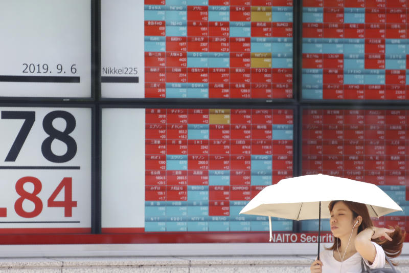A woman walks by an electronic stock board of a securities firm in Tokyo, Friday, Sept. 6, 2019. Asian shares rose Friday as investors cheered plans for more trade negotiations between Washington and Beijing and drew encouragement from positive data about the U.S. economy. (AP Photo/Koji Sasahara)