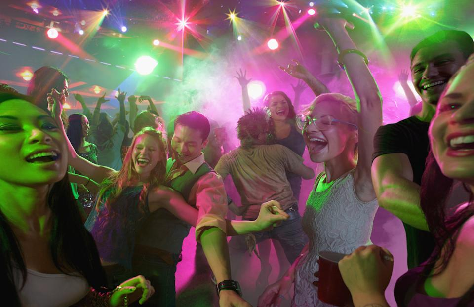 Young people dancing and having fun in a large nightclub.