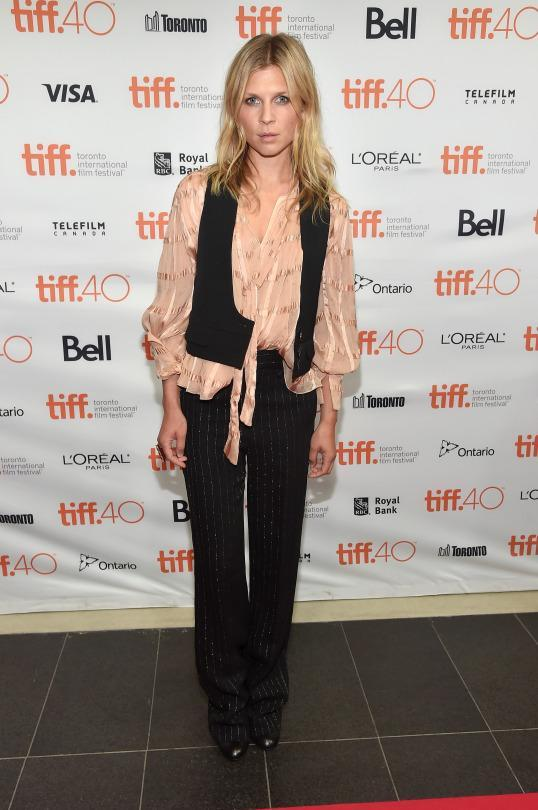 "<p>Clemence Poesy mixed business casual — pinstripe trousers and vest— with just plain casual with glitter stripes and a peasant blouse at ""The Ones Below"" photo call.</p>"