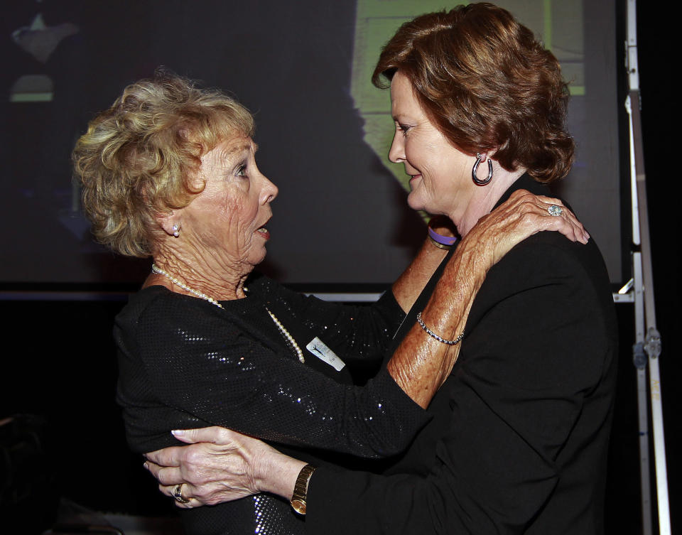 FILE - In this April 25, 2012, file photo, former Tennessee women's basketball coach Pat Summitt, right, embraces Nan Wooden, daughter of famed UCLA men's basketball coach John Wooden, before accepting the Coach Wooden Citizenship Cup by Athletes for a Better World in Atlanta. Nan Wooden died Tuesday, Sept. 14, 2021. She was 87. The school said she died of natural causes at a care facility in the San Fernando Valley, according to family members. She had suffered a series of strokes in recent years. (AP Photo/John Bazemore, File)