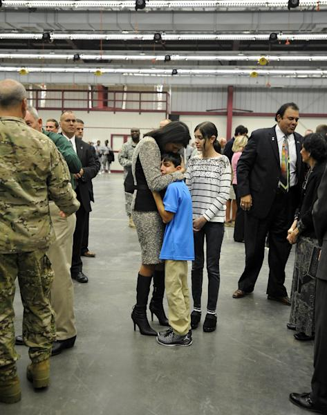 South Carolina Gov. Nikki Haley, center, comforts her son, Nalin, 10, and her daughter, Rena, 14, as her husband, Michael Haley, far left, gets ready for a deployment ceremony for the South Carolina Army National Guard 3/49 Agribusiness Development Team at McCrady Training Center, Thursday, Jan. 10, 2013, at Ft. Jackson, S.C. The deployment is scheduled for a year including one month of training in Indiana prior to leaving for Afghanistan. (AP Photo/Rainier Ehrhardt)