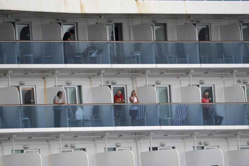 Passengers look out from the Coral Princess cruise ship while docked in Miami, Monday, April 6, 2020. Authorities say 14 people have been taken to hospitals from the cruise ship that docked in Florida with coronavirus victims aboard and one of them has died at a hospital. Two fatalities were reported earlier aboard the Coral Princess. The Coral Princess had more than 1,000 passengers and nearly 900 crew members. It began disembarking fit passengers Sunday. Any with symptoms of COVID-19 or recovering were being kept on ship until medically cleared. (AP Photo/Wilfredo Lee)