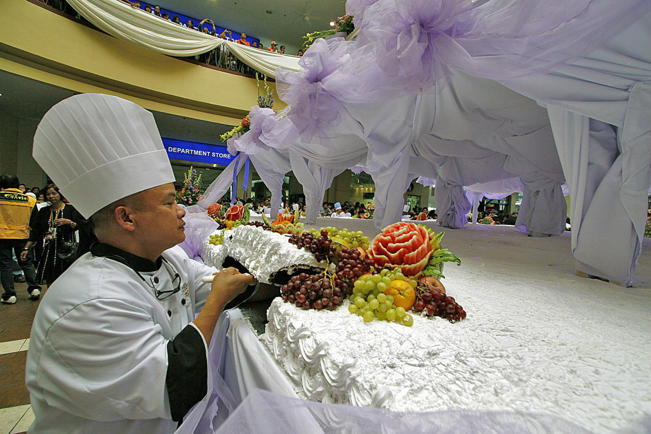 BIG SERVINGS - Pastry Chef Art Nocasa of Baguio Country Club slices portions of a three-ton chocolate cake during the opening of the Hotel, Restaurant and Tourism Week in Baguio City Thursday. The 28-feet tall, 24.5-feet wide cake is supposedly enough for 10,000 people. (NPPA Images)