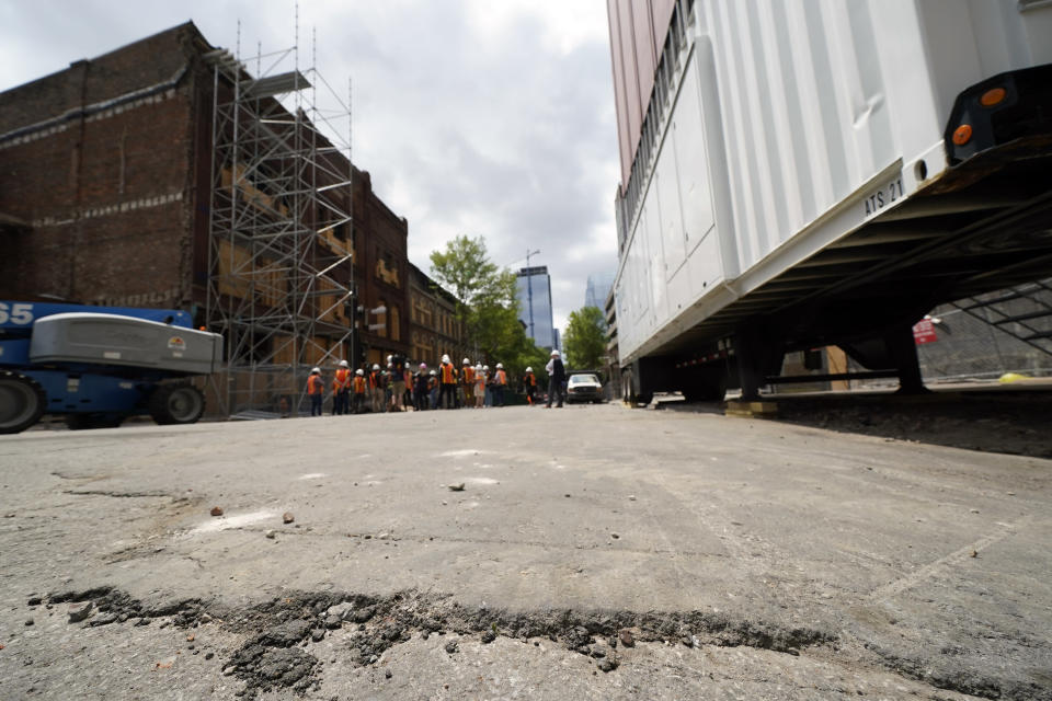 An asphalt patch fills the hole in the street in front of an AT&T office building Friday, June 25, 2021, where a recreational vehicle containing explosives blew up in a suicide bombing on Christmas Day, 2020, in Nashville, Tenn. Six months after the bombing ripped a hole in historic downtown, workers continue to chip away at cleanup efforts so that revitalization can begin. The tediously slow process has meant workers haven't been able to access some of the buildings until recent weeks. (AP Photo/Mark Humphrey)