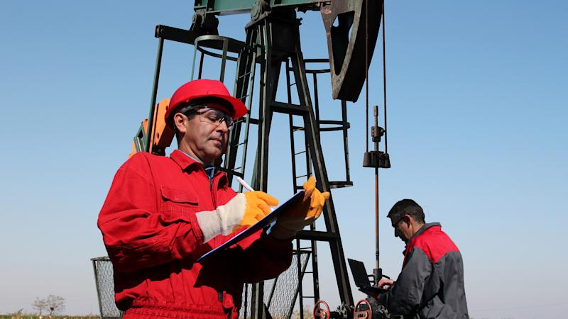 Two men working with an oil well in the background