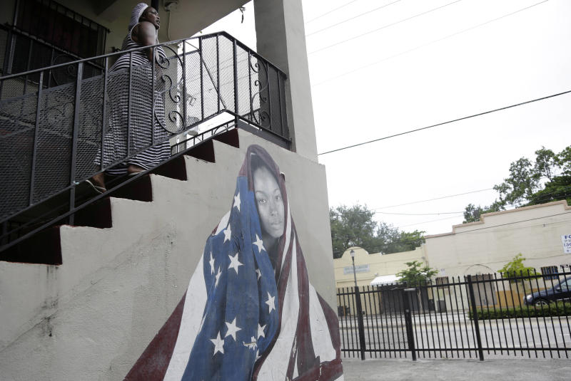 In this photo taken July 1, 2013, a woman walks up a stairway of an apartment building decorated with a mural on Grand Avenue in the Village West neighborhood of Coconut Grove in Miami. The community, settled by Bahamian immigrants in the 1880's, was the first black settlement in South Florida. It has suffered from many years of decline and lack of investment. This building is among six blocks of Grand Avenue which are part of a $306 million redevelopment plan proposed by Point Group Advisors to build retail, office, and residential space. (AP Photo/Lynne Sladky)