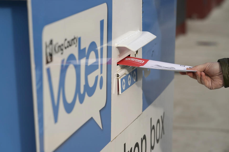 FILE - A person puts their ballot in a drop box at a library in Seattle's White Center neighborhood on Oct. 27, 2020. Television networks are adding experts in election law to their election night coverage teams so they're prepared to explain legal challenges or irregularities that come up during the vote. (AP Photo/Ted S. Warren, File)