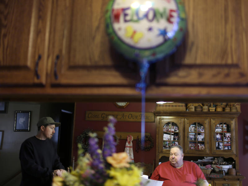 In this photo made Feb. 20, 2013, Mark Woodworth, left, talks with his father Claude Woodworth as a balloon let over from Mark's welcome home party still floats in their kitchen in Chillicothe, Mo. Mark Woodworth, whose murder conviction in the 1990 slaying of a neighbor was recently overturned by the Missouri Supreme Court, was recently set free on bond allowing him to return home for the first time in 13 years while waiting to be tried for a third time in case. (AP Photo/Jeff Roberson)