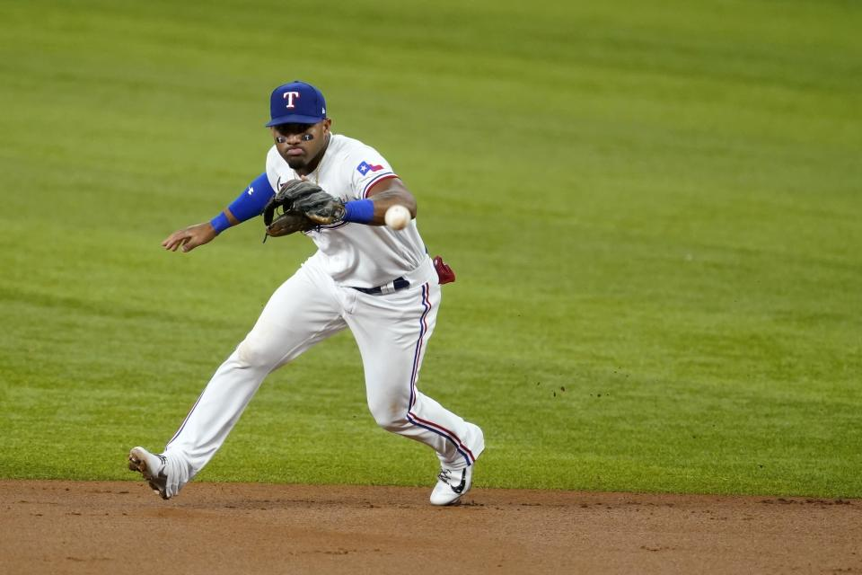 Texas Rangers second baseman Andy Ibanez fields a grounder by Seattle Mariners' Jarred Kelenic, who was out at first during the second inning of a baseball game in Arlington, Texas, Saturday, July 31, 2021. (AP Photo/Tony Gutierrez)